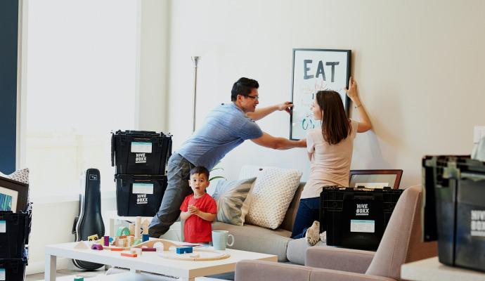 Mor, far og sønn som har nettopp flyttet inn og henger opp bilde på veggen.